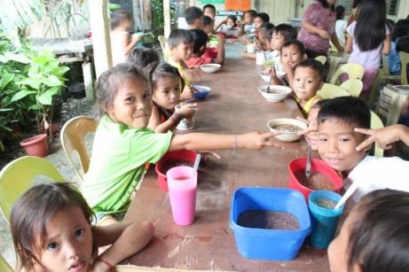 Filipino children enjoying lunch at the Kid's Freedom Center